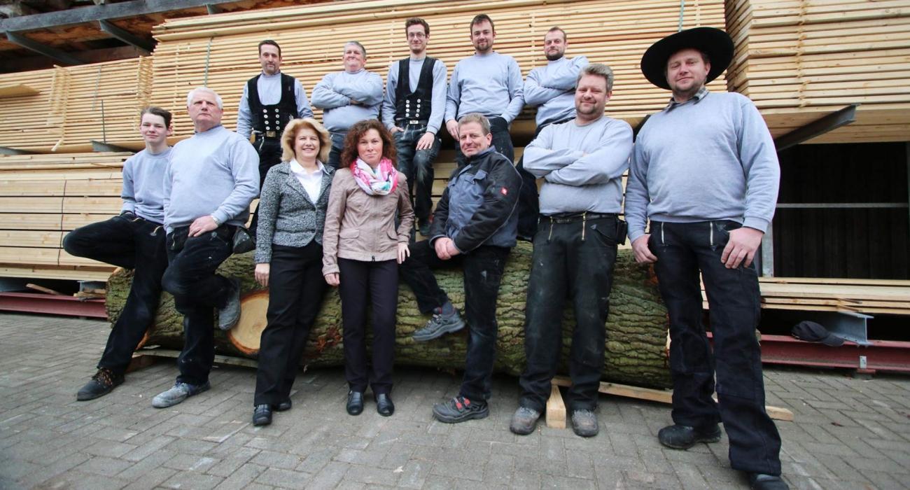 Foto der Mitarbeiter der Zimmerei Schaper vor einen Stapel Holzlatten
